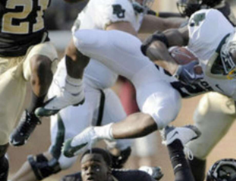 Wake Forest cornerback Kenny Okoro (bottom) loses his helmet as Baylor running back Jay Finley (top) is tripped up while running for a first down during the fourth quarter on Saturday. Finley ran for 91 yards on 14 attempts in the 24-21 victory in Winston-Salem, N.C.