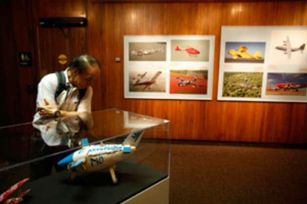 "Mitsunori Miki examines a folk art airplane from Nepal, one of many featured in the new exhibit ""A Salute to Military Flight,"" at the Institute of Texan Cultures."