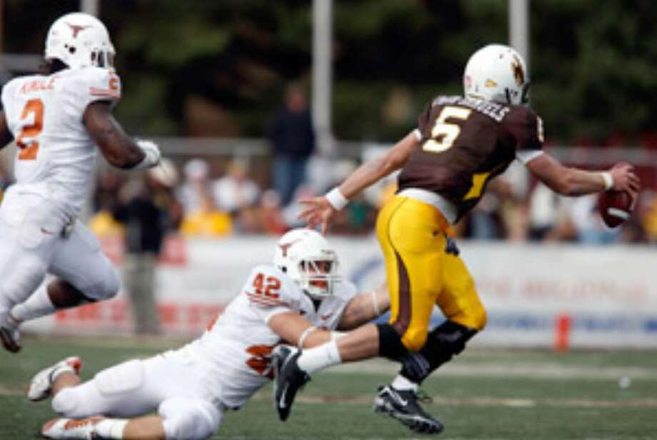 Texas' Sergio Kindle (left) trails as teammate Dustin Earnest drags down Wyoming's Austyn Carta-Samuels.