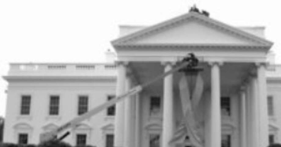A pink ribbon to recognize breast cancer awareness is hung on the White House.