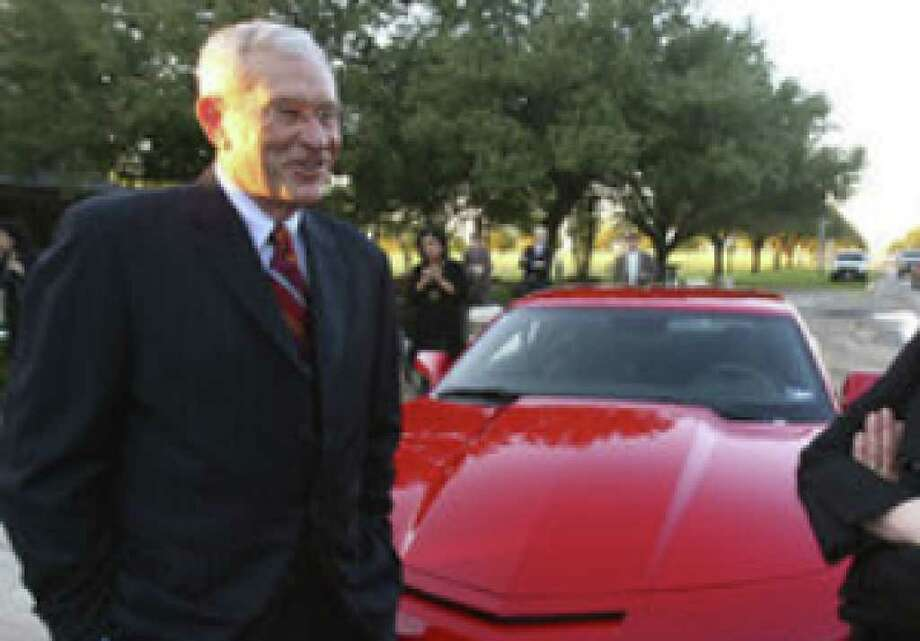 General Motors Chairman Edward Whitacre Jr. and Texas Lutheran University President Ann Svennungsen share a laugh in front of a new Camaro brought in for his speaking engagement at the school in Seguin.