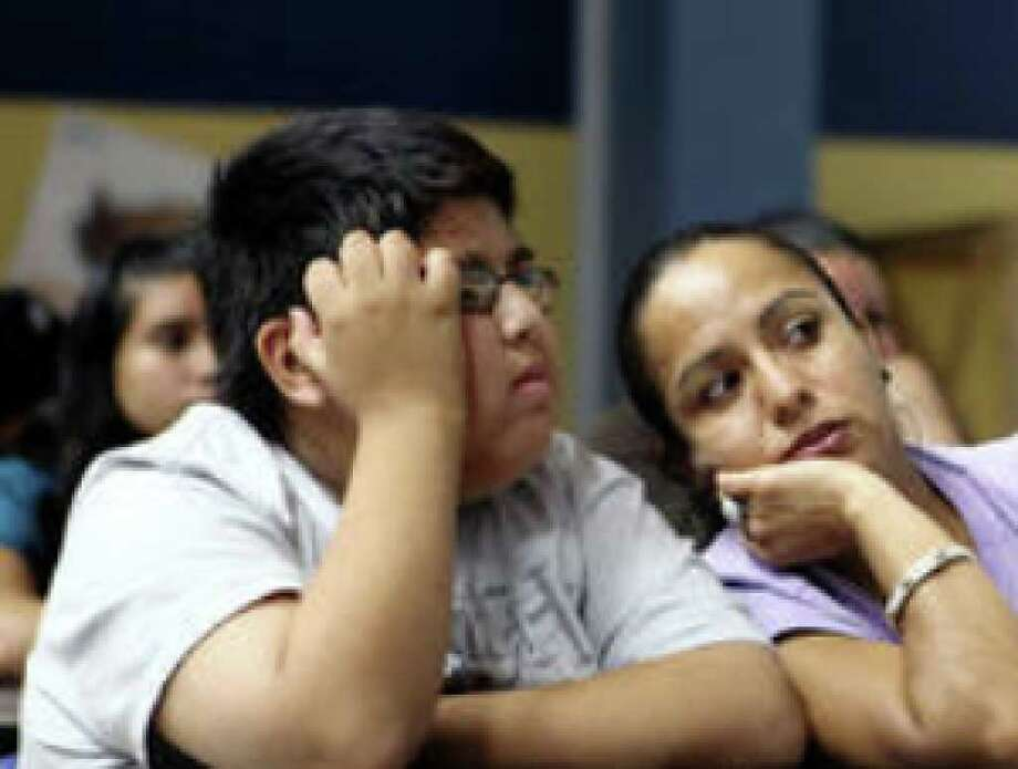 Maria Vazquez whispers to son Juan Jesus Vazquez, 12, during a meeting at Dwight Middle School on teen sexual activity.