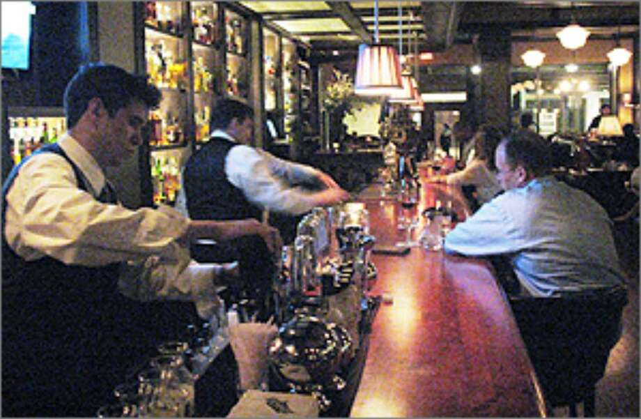 Bartender Jake Corney (left) and his colleagues serve a dizzying array of drinks at the Bar at Bohanan's.