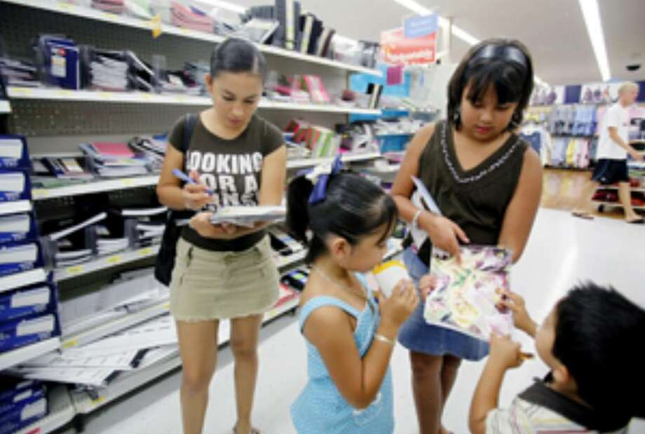 Daisy Elizando (from left) checks a list of school supplies for her children Stacy Elizondo, 6, Karina Iracheta, 11, and Axel Elizondo, 4.