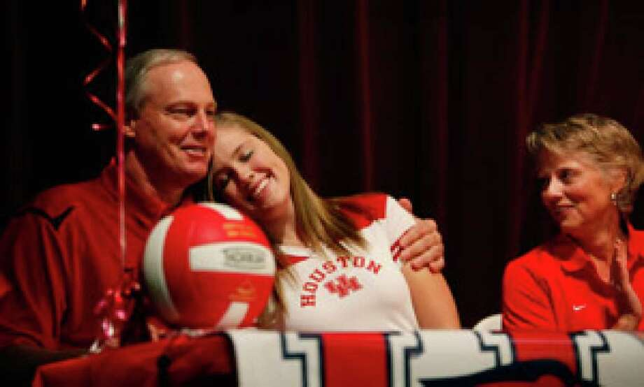 Reagan volleyball player Kacy Griffin, flanked by father, ex-Spur Paul Griffin, and mother, Kim Griffin, makes it official during the early signing period by choosing the University of Houston. She was one of seven Reagan athletes and several others around the area signing scholarship letters Wednesday.