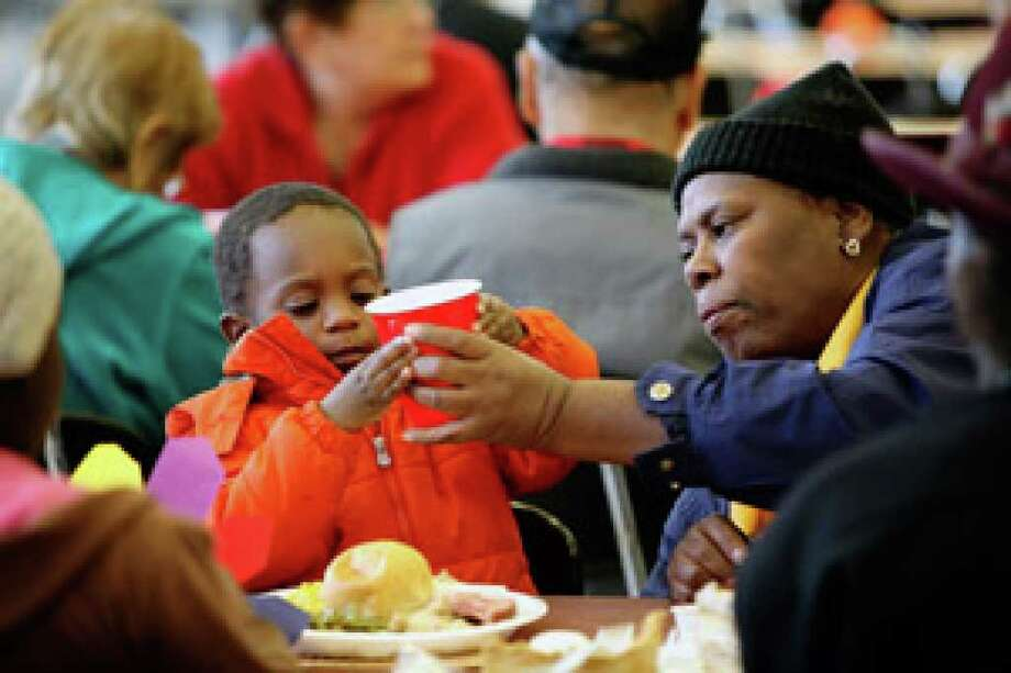 Trea Byrd, 2, gets help with his drink from great-grandmother Audrey Byrd during the Thanksgiving Community Feast at Wagner High School. The event is the result of a suggestion by Chris Pryor, the founder of Fatty's Burgers and More.