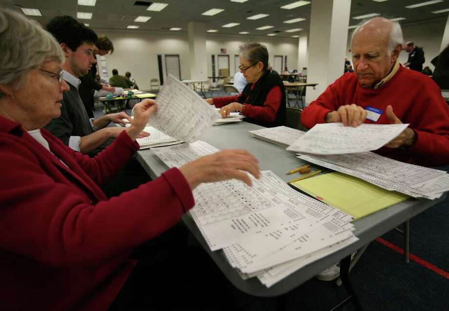From left; Volunteers Barbara Thorne of Darien, Bryant Madden of Essex, Zazu Gray of Milford, and Gray's husband Nicholas Pyndus of Milford, examine ballots as part of the election recount at the City Hall Annex in Bridgeport on Tuesday, November 30, 2010. Photo: Brian A. Pounds / Connecticut Post