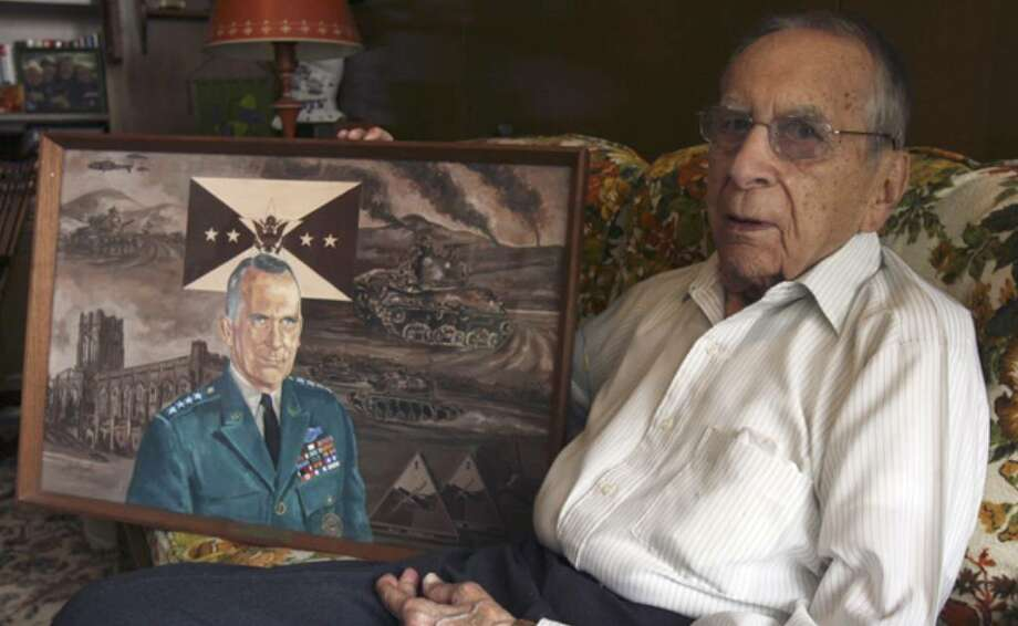 Retired Army Gen. Ralph Haines shows a portrait commemorating his military career. On the left side of the painting is the chapel at West Point. Haines will be the only member of the U.S. Military Academy's class of 1935 attending a reunion of several classes this week.