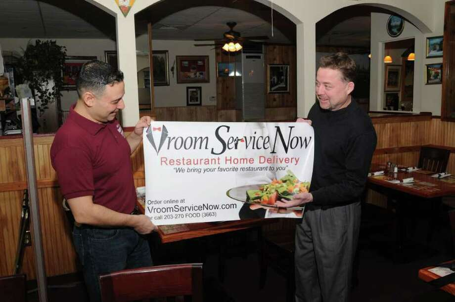 Augie Incorvaia, left, owner of Augie's Numero Ono Pizzeria, in Danbury, and Vroom Service Now owner Scott Leandra hold a banner, on Monday, Nov. 20, 2010.  Augie's  Pizzeria is just one of the local restaurants that uses the Vroom Service Now delivery service. Photo: Jay Weir / The News-Times Freelance