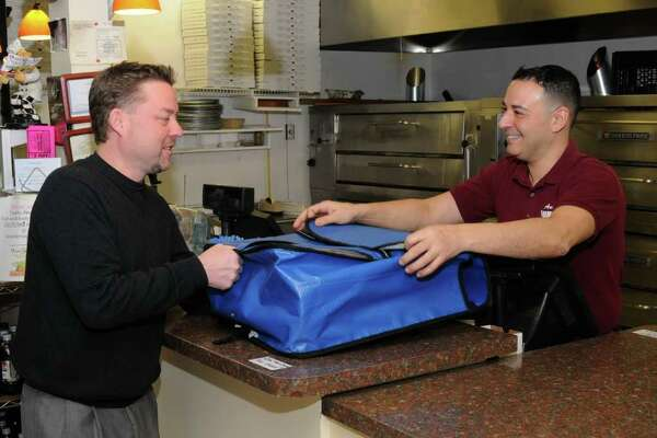 Vroom Service Now is a delivery service for restaruants. Owner Scott Leandra, left, picks up an order from Augie Incorvaia, owner of Augie's Numero Uno Pizzeria in Danbury, on Monday, Nov. 29, 2010.