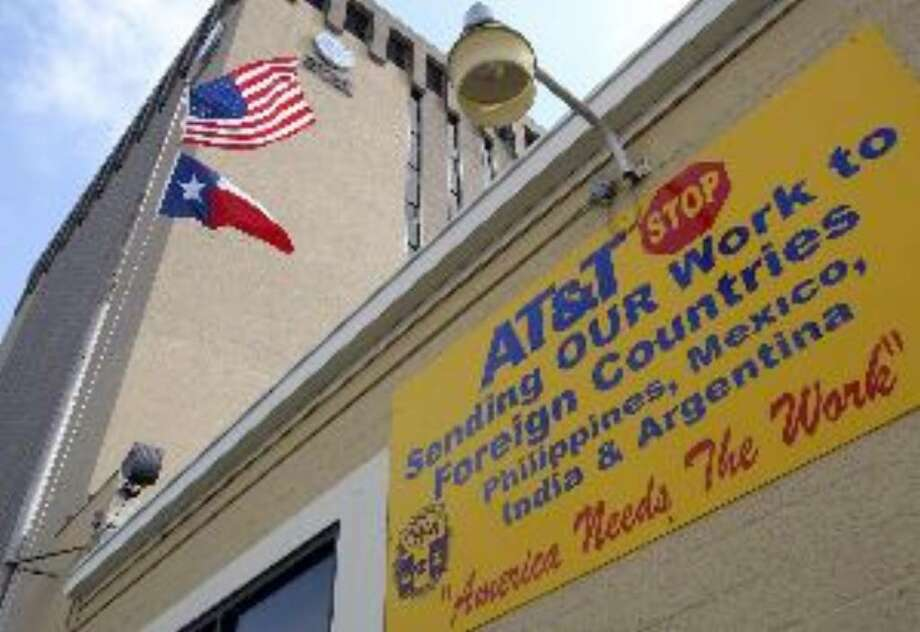 A sign on the Communications Workers of America building tells A&T to stop outsourcing jobs.