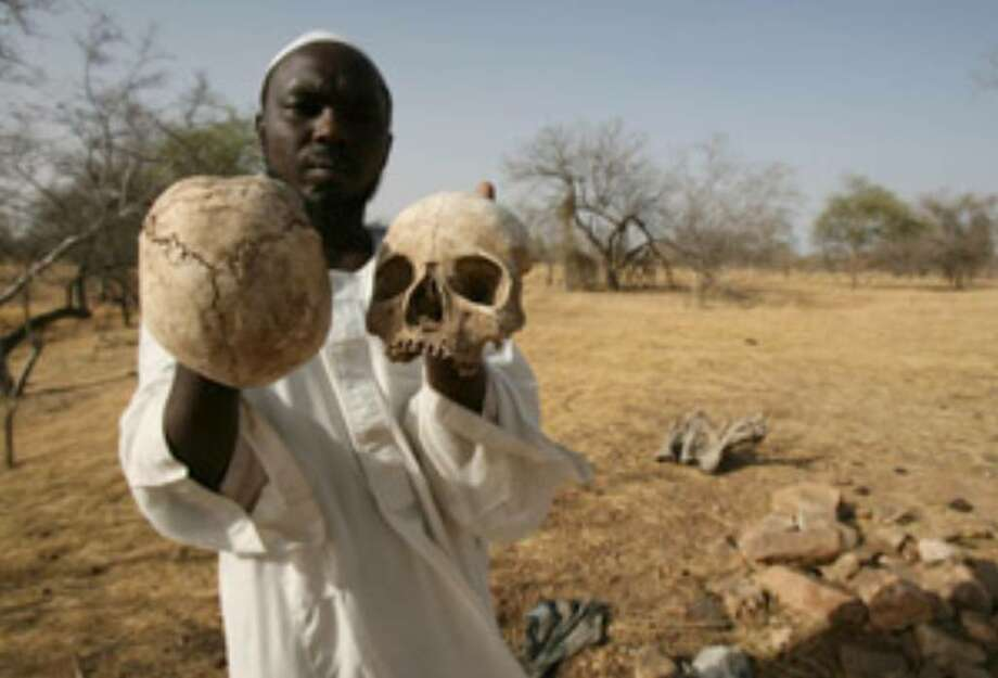 A Darfur survivor shows human skulls at a mass grave in 2007. Not much has changed since then.