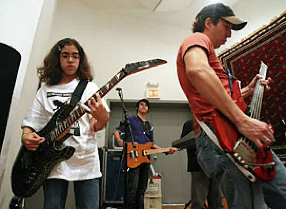 Emily Gamez, 12 rehearses with her instructor Michael Morales. Gamez is part of a group of young rockers who will debut at Sam's Burger Joint Tuesday.