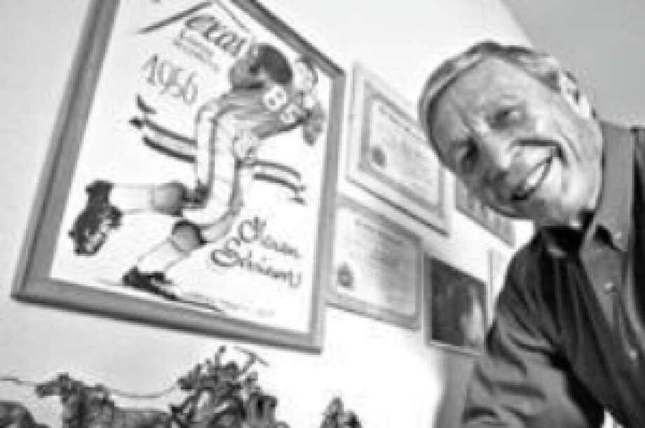 Menan Schriewer, who played seven years in the CFL, shows off his 1956 Longhorns poster at home on Nov. 19, 2009.