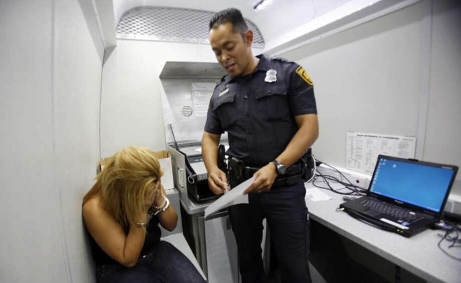 A DWI suspect reacts as Officer Gabriel Gallegos, a patrolman with the DWI unit, tells her the results of a breathalyzer test.