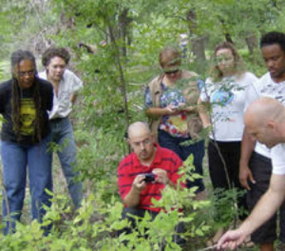 Wilderness First Aid instructor Sam Coffman (far right in shorts) shows students what poison oak looks like in a field behind the Helotes Creek Nature Center. The students are (from left) Gloria Rupert, Marcia Valvo, James Hernandez (kneeling), Sara Holland-Adams, Felicia Latteo, Devin Martin and Mike Avery.