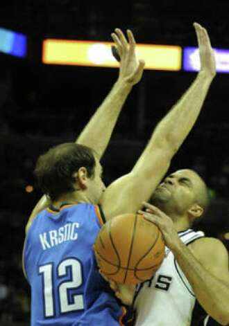 The Spurs' Tony Parker plows into the Thunder's Nenad Krstic as he drives to the basket during the first half Saturday night at the AT&T Center.