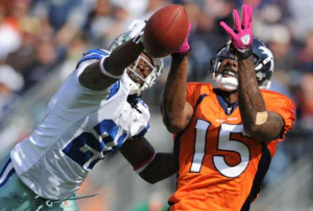 Cowboys cornerback Mike Jenkins (left) breaks up a pass intended for Broncos wide receiver Brandon Marshall on Sunday during Denver's victory. The loss sent the Cowboys to 2-2, but owner Jerry Jones says he's not discouraged by the record.