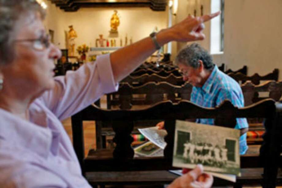 Alumnae and reunion organizers Mary Geigenmiller Anderson (left) and Janie Garza sort through pictures of students at the San Francisco de la Espada School at Mission Espada.