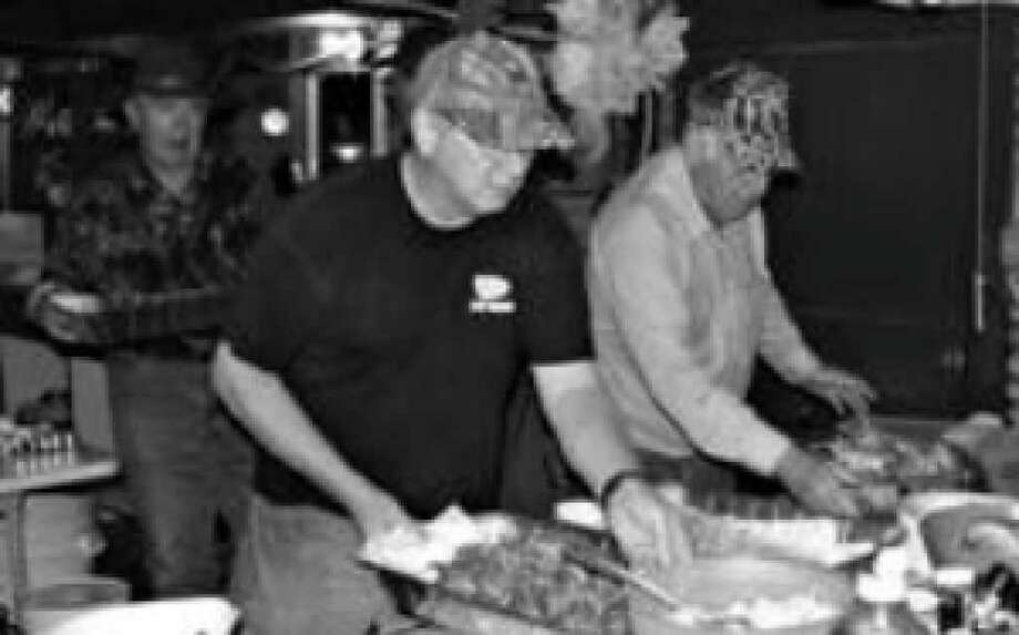 John Oppenheimer (right) and Jim Raby set out trays of fresh fried shrimp and oysters during a typical meal at the Herbert M. Oppenheimer Ranch.