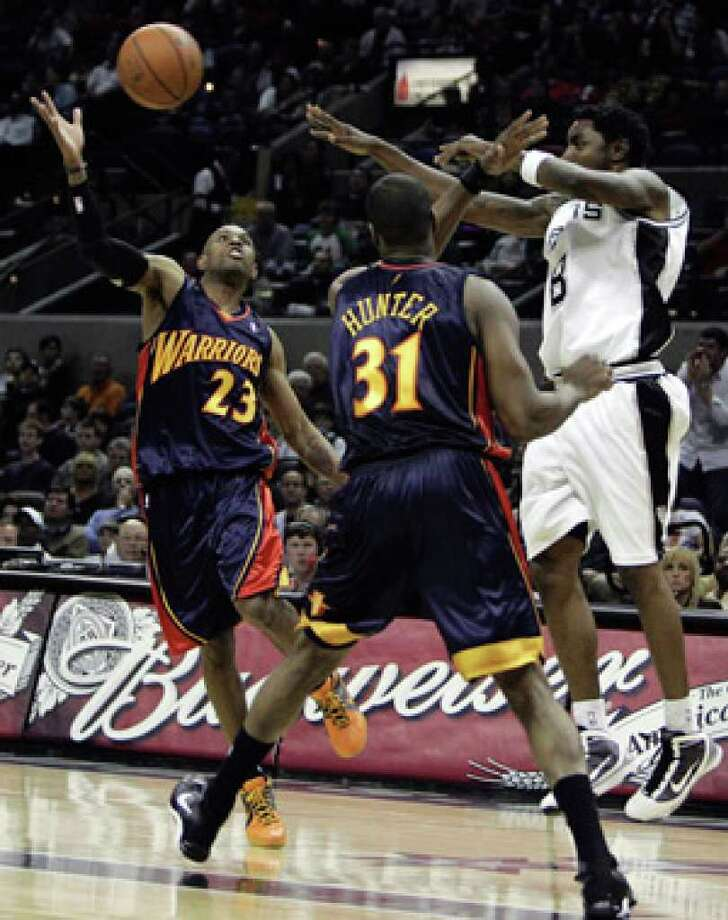 Spurs guard Roger Mason Jr. (right) passes over Warriors defenders C.J. Watson (left) and Chris Hunter on Wednesday.