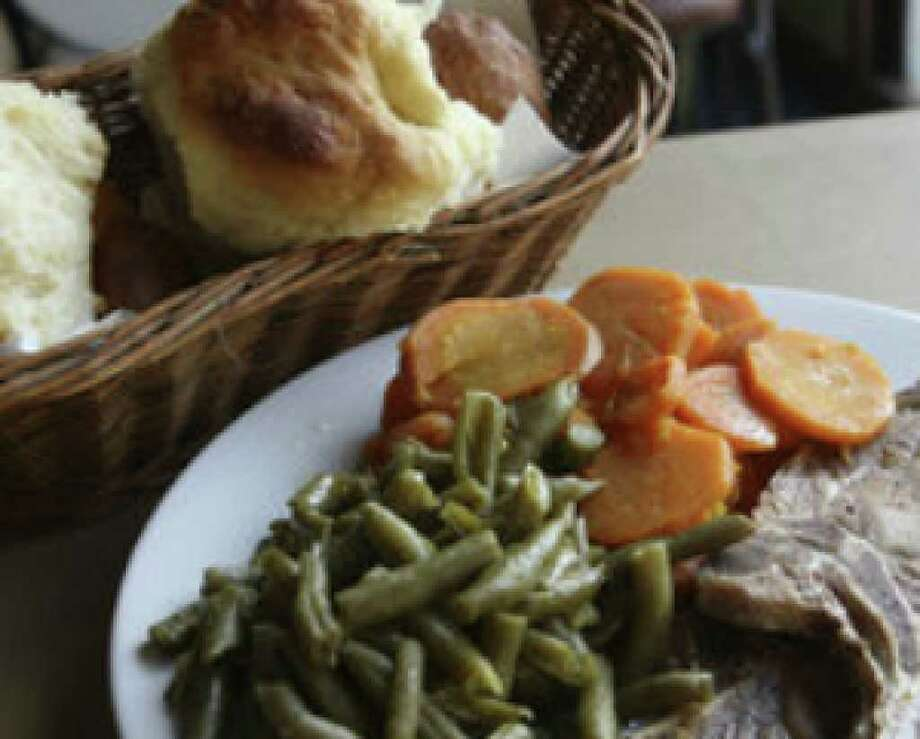 A plate of grilled pork chops, carrots and beans and a basket of dinner rolls await diners at Mr. Tim's Country Kitchen.