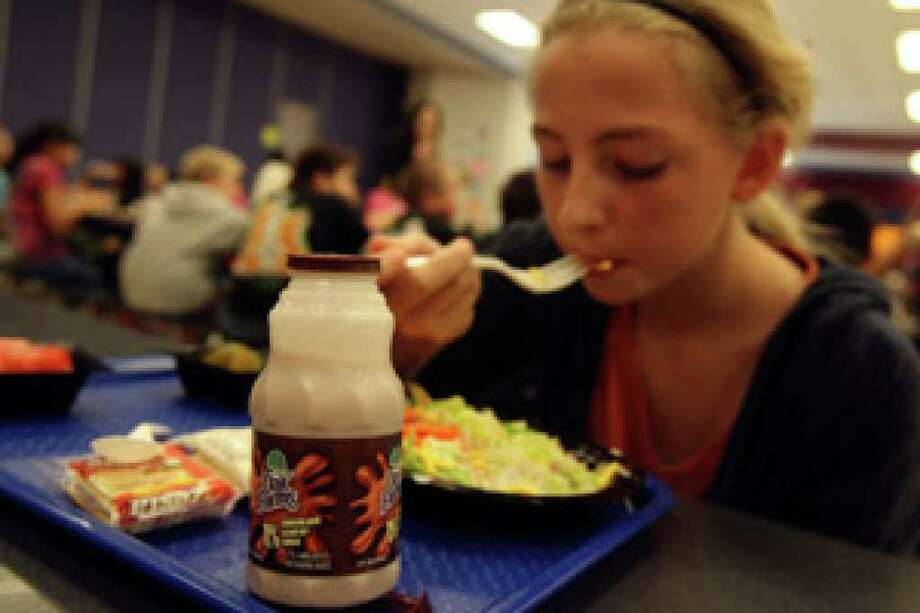 Carly Norment ,10, a fifth-grader at Wetmore Elementary, enjoys a salad and a bottle of chocolate milk at lunch. Some officials say the extra sugar is the last thing kids need.