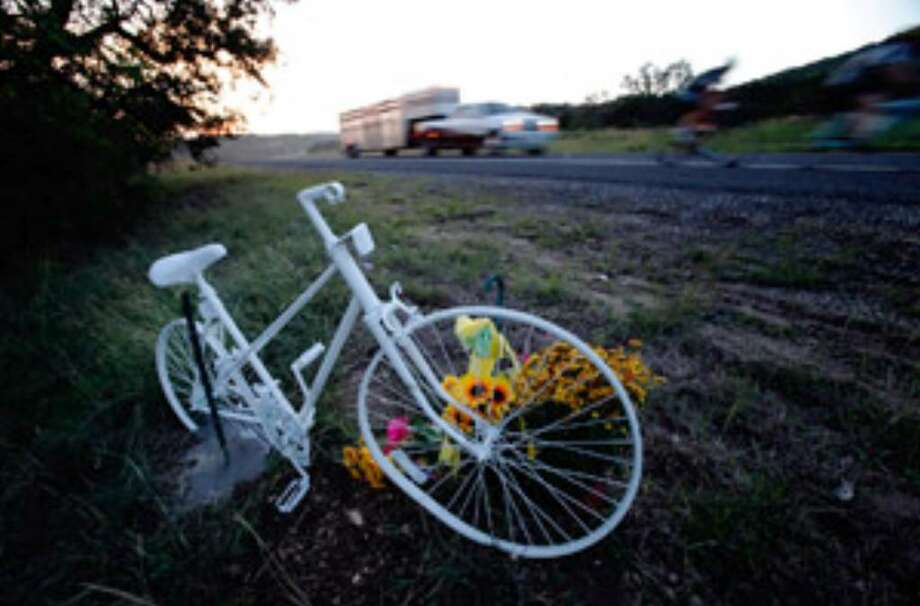 A white-painted bicycle marks the spot on Texas 16 near Helotes where bicyclists Gregory Bruehler, 42, and his 36-year-old wife, Alexandra, died after being hit by a pickup.