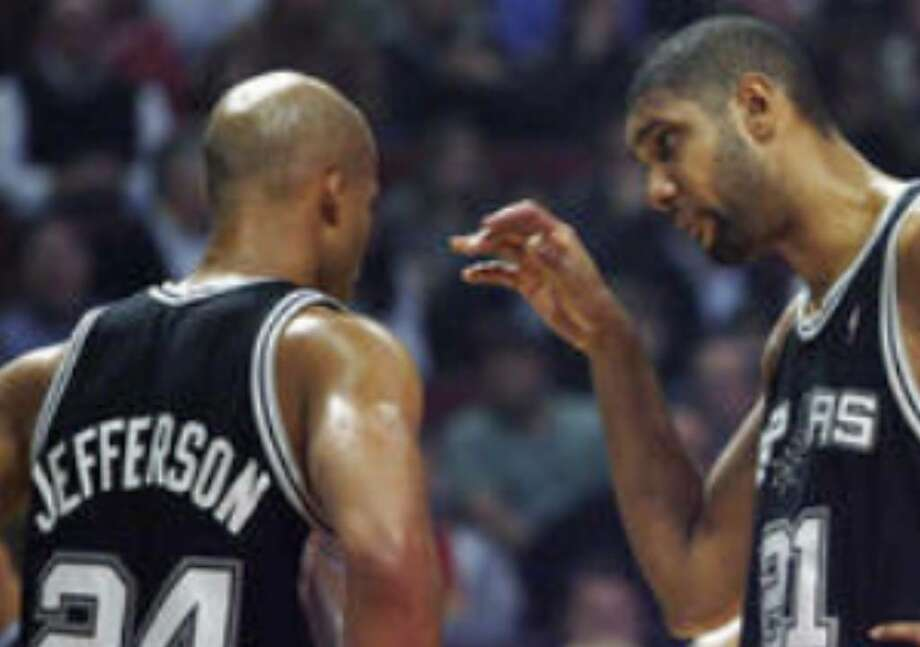 Tim Duncan speaks Thursday to Richard Jefferson, who is one of six new players trying to learn the Spurs' system and jell with veterans.