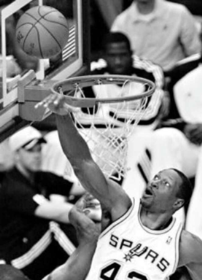 Center Theo Ratliff rejects a shot by Utah's Ronnie Brewer in the first half, one of his three blocked shots.