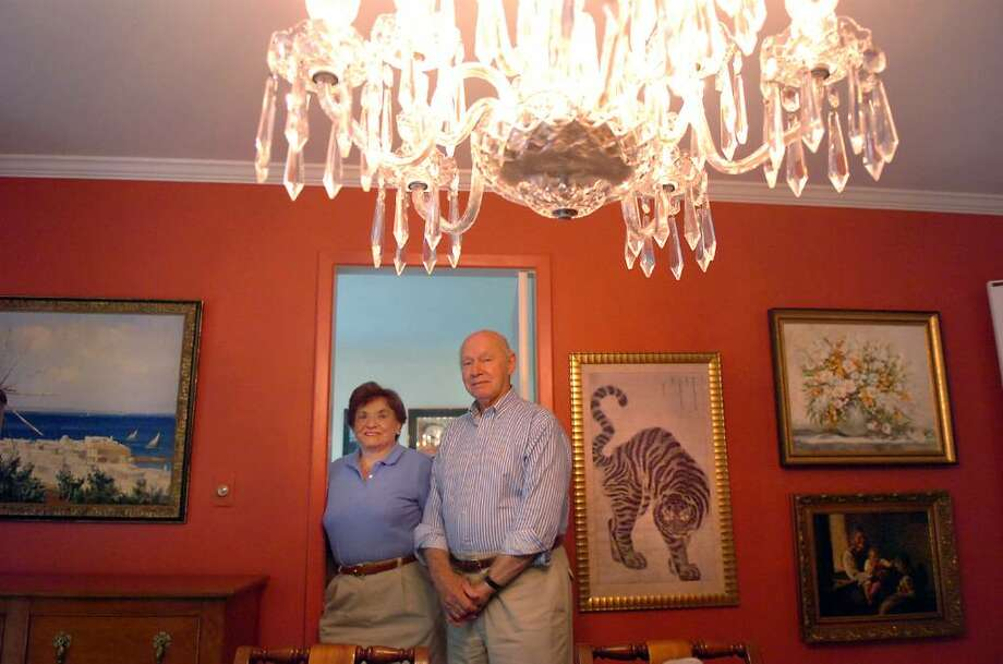 Barbara and Timothy Nolan lit by their Waterford Crystal chandelier in their Greenwich home Saturday afternoon, Aug. 29, 2009. They designed and built the 4,700 square foot home in 1977 and are now selling it as they downsize in retirement. The house sits on 1.3 acres one mile from dowtown. Photo: Keelin Daly / Greenwich Time