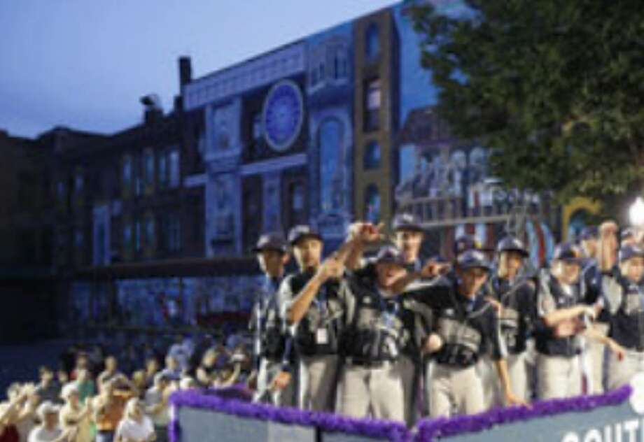 McAllister Park Little League players, wearing their Southwest regional representatives uniforms, ride on a float in the fifth annual Grand Slam Parade through Williamsport, Pa.