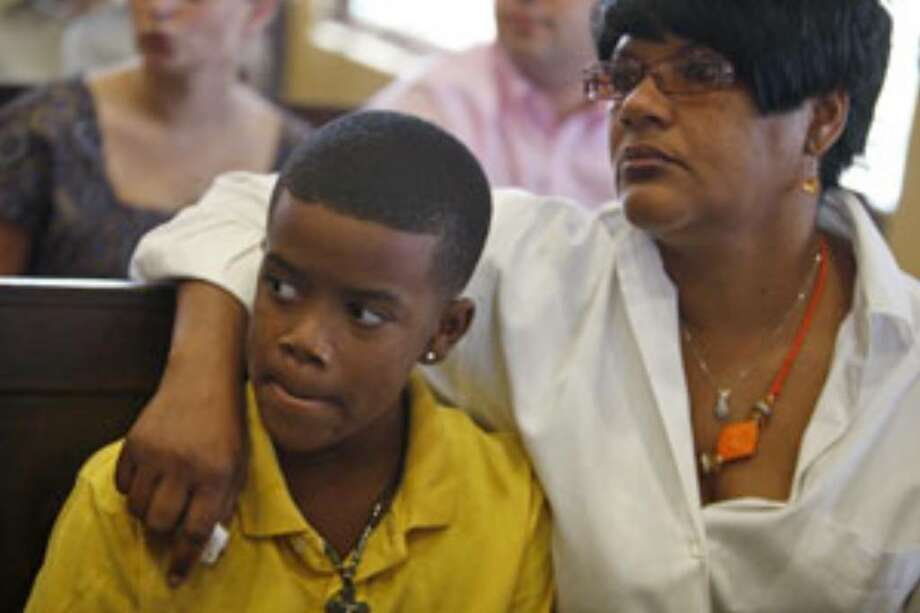 Marcus Richard, 9, the nephew of Michael Richard, and his grandmother and Michael's sister, Betty Richard, wait for day three of the fact finding hearing for Judge Sharon Keller to begin at the Bexar County Courthouse on Wednesday.