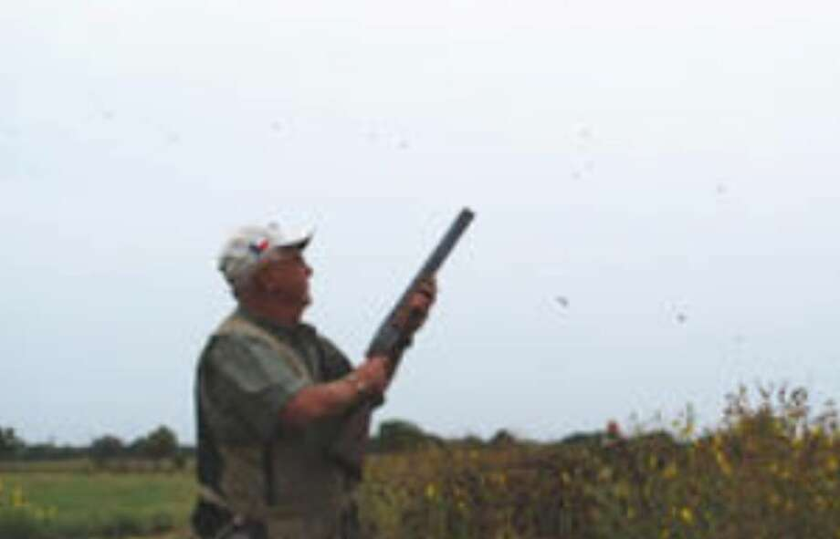 Tom Green of San Antonio, hunting with a group of hunters from Vulcan Materials, is surrounded by huge flights of white-winged doves flocking to a field at the Nooner Ranch near Hondo on Tuesday's opening day of the Central Zone dove season.