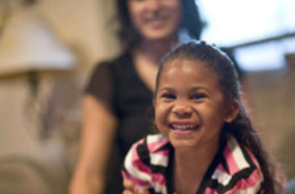 Five-year-old Jasalyn laughs while playing with a coloring book with her foster parents, Yolanda and Carl Deaton, at their home in Arlington. Jasalyn's biological mother, Tracy Rhine, has taken her case to the U.S. Supreme Court.