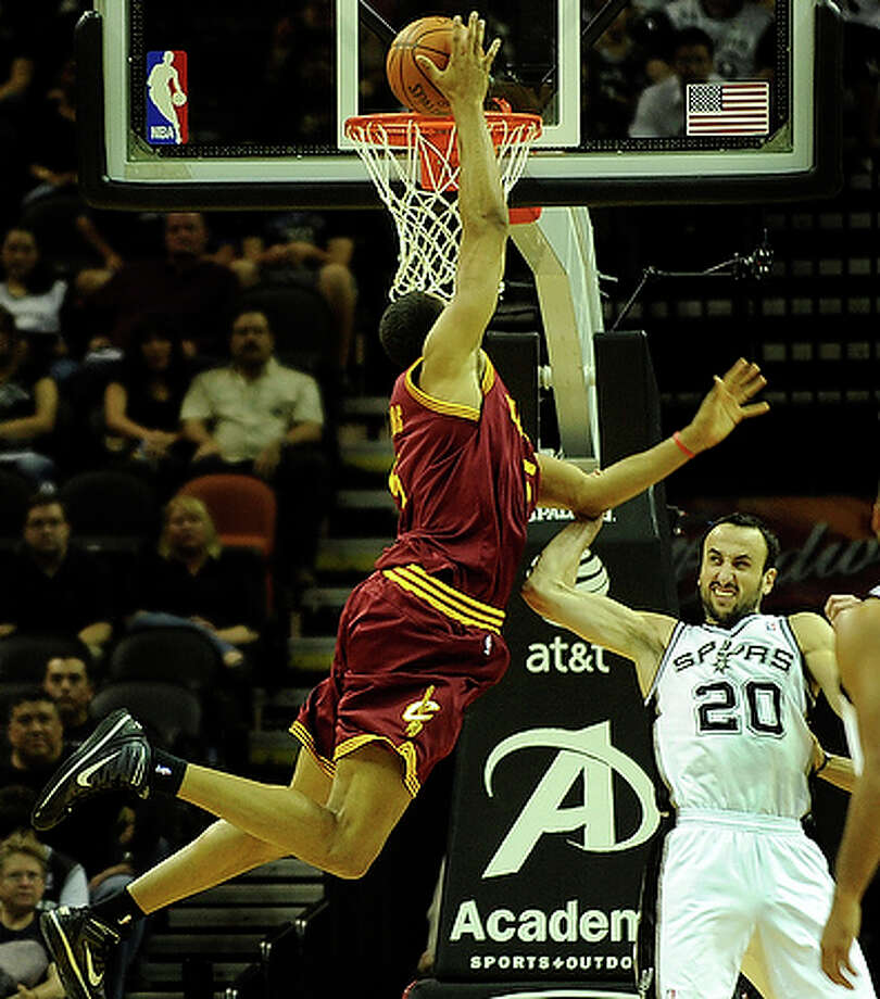 Ryan Hollins of the Cleveland Cavaliers shoots as he is fouled by Manu Ginobili (20) of the San Antonio Spurs.
