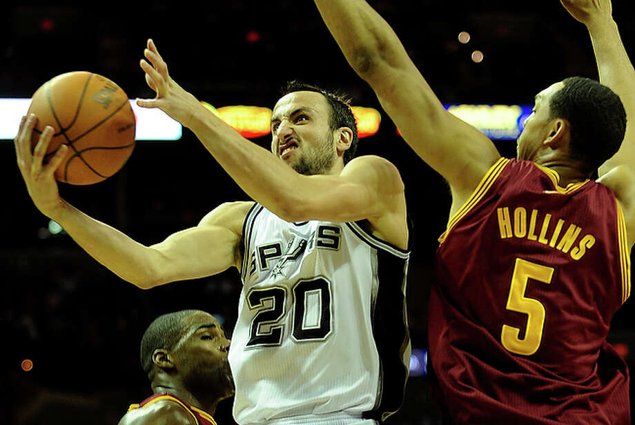 Manu Ginobili of the San Antonio Spurs drives by Ryan Hollins of the Cleveland Cavaliers.