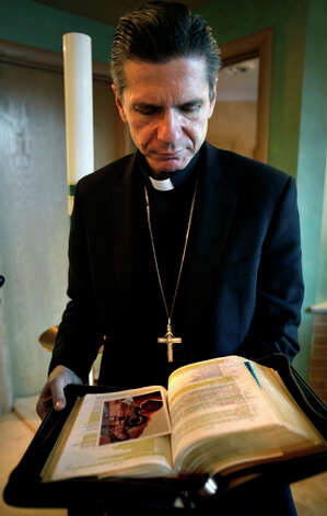 Archbishop Gustavo Garcia-Siller, looks through his heavily highlighted Bible in his private Chapel in his Chicago office. / rowen@express-news.net