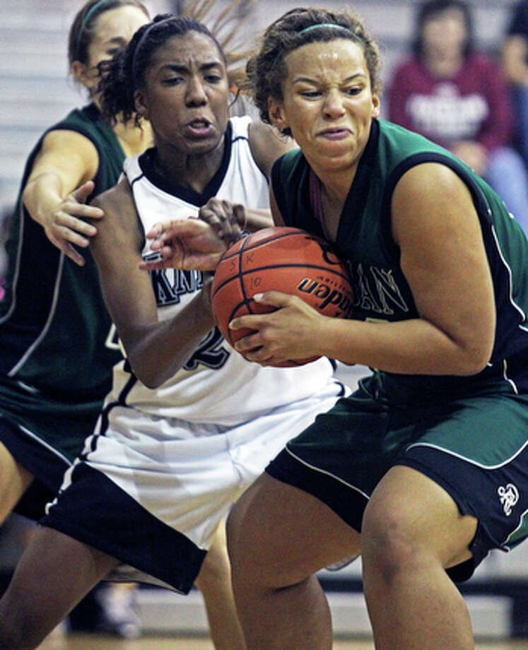 Reagan's Corrigan Tibbs muscles a defensive rebound away from the Knights' Taylor Calvert during game action in Steele's 74-54 win at Steele gym on Nov. 16, 2010. / © 2010 San Antonio Express-News