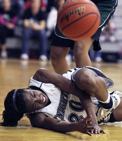Taylor Calvert contorts on the floor as she saves a loose ball and passes for Steele. / © 2010 San Antonio Express-News