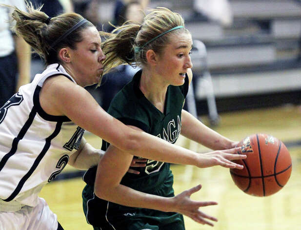 Reagan's Wendy Knight is challenged on the dribble in the lane by Steele's Lauren Zoldey. / © 2010 San Antonio Express-News
