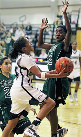 Steele's Elena Gumbs sneaks in to the basket past Tessa Ramirez only to be challenged underneath by Moriah Mack. / © 2010 San Antonio Express-News