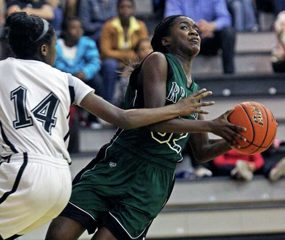 Reagan's Moriah Mack gets slapped on the arms as she drives against McKenzie Calvert. / © 2010 San Antonio Express-News