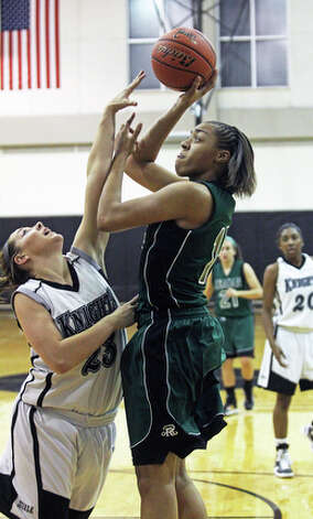 Reagan's Sabrina Berry puts up a shot on the baseline against Lauren Zoldey. / © 2010 San Antonio Express-News