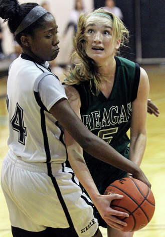 Reagan's Wendy Knight is fouled on her way to the basket by Steele's McKenzie Calvert. / © 2010 San Antonio Express-News