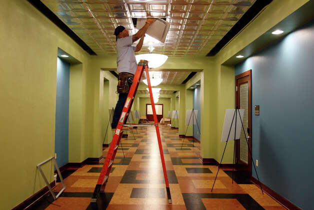 Chris Alvarado installs air conditioning vents on the second floor hallway. / glara@express-news.net