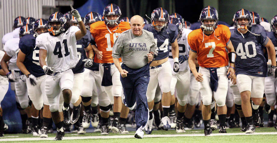 UTSA's head coach Larry Coker (center) leads the team onto the field Thursday Nov 18, 2010 before the scrimmage at the Alamodome. / eaornelas@express-news.net