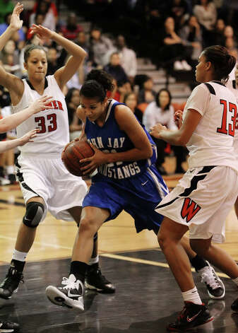 John Jay's Erika Donovan (21) drives into the paint against Wagner's Arielle Roberson (33) and Kiara Rivera (13). / kmhui@express-news.net