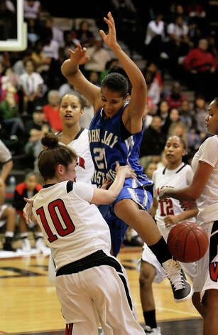 John Jay's Erika Donovan (21) gets fouled as she goes for a shot in the paint by Wagner's Corinna Moncada (10). / kmhui@express-news.net