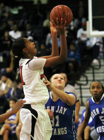 Wagner's Eboni Watkins (11) takes a shot against John Jay's Vanessa Orr (31). / kmhui@express-news.net